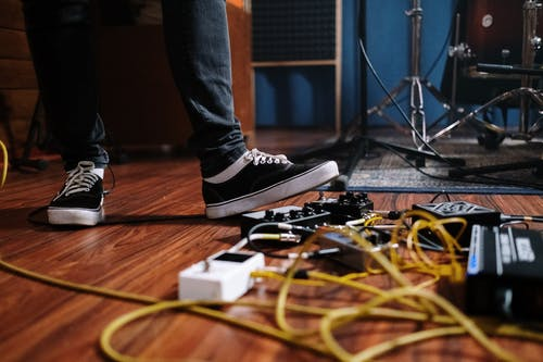 Person Wearing Black and White Nike Sneakers Standing on Black and White Guitar Effect Pedal