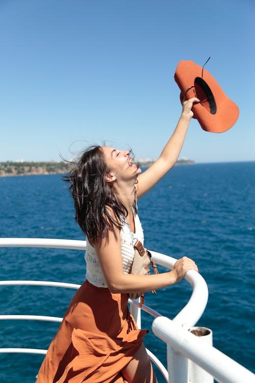 Stylish female standing near railings against sea