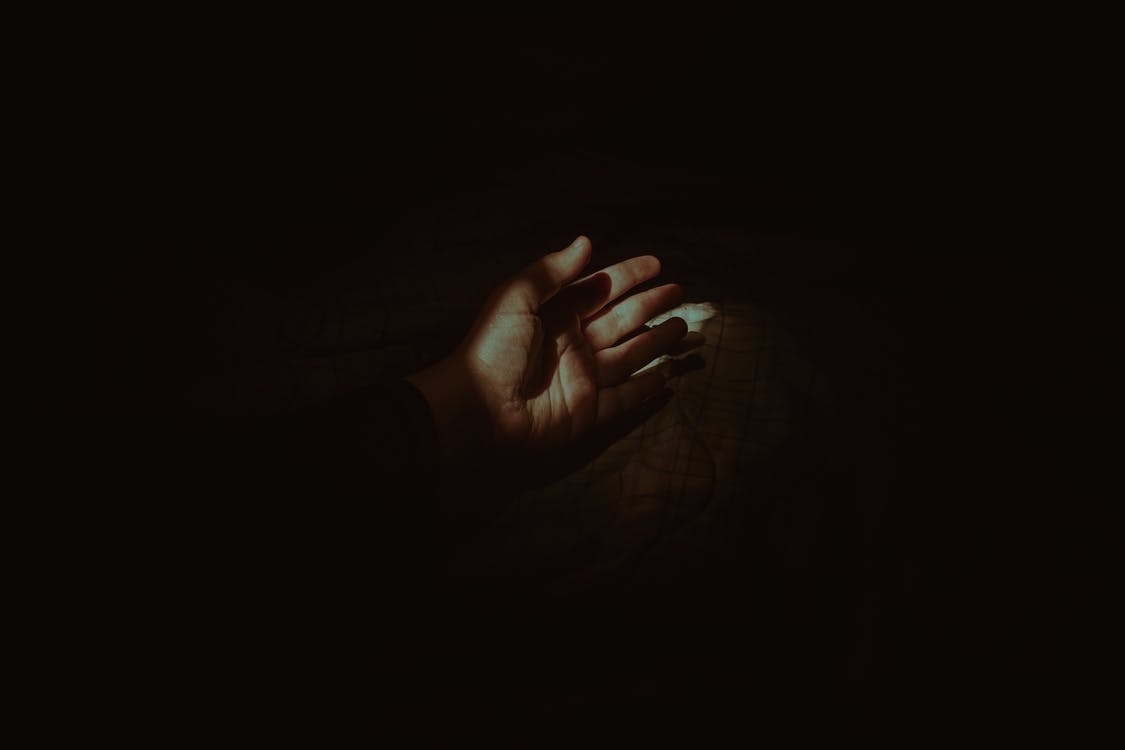 Crop anonymous person hand lying on cozy soft bed in dark bedroom with beam of light