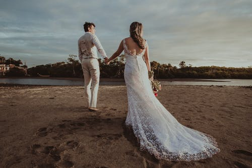 Bride and groom walking on sandy coastline