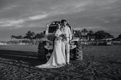 Black and white of bride and smiling groom standing in front of SUV parked on sandy field