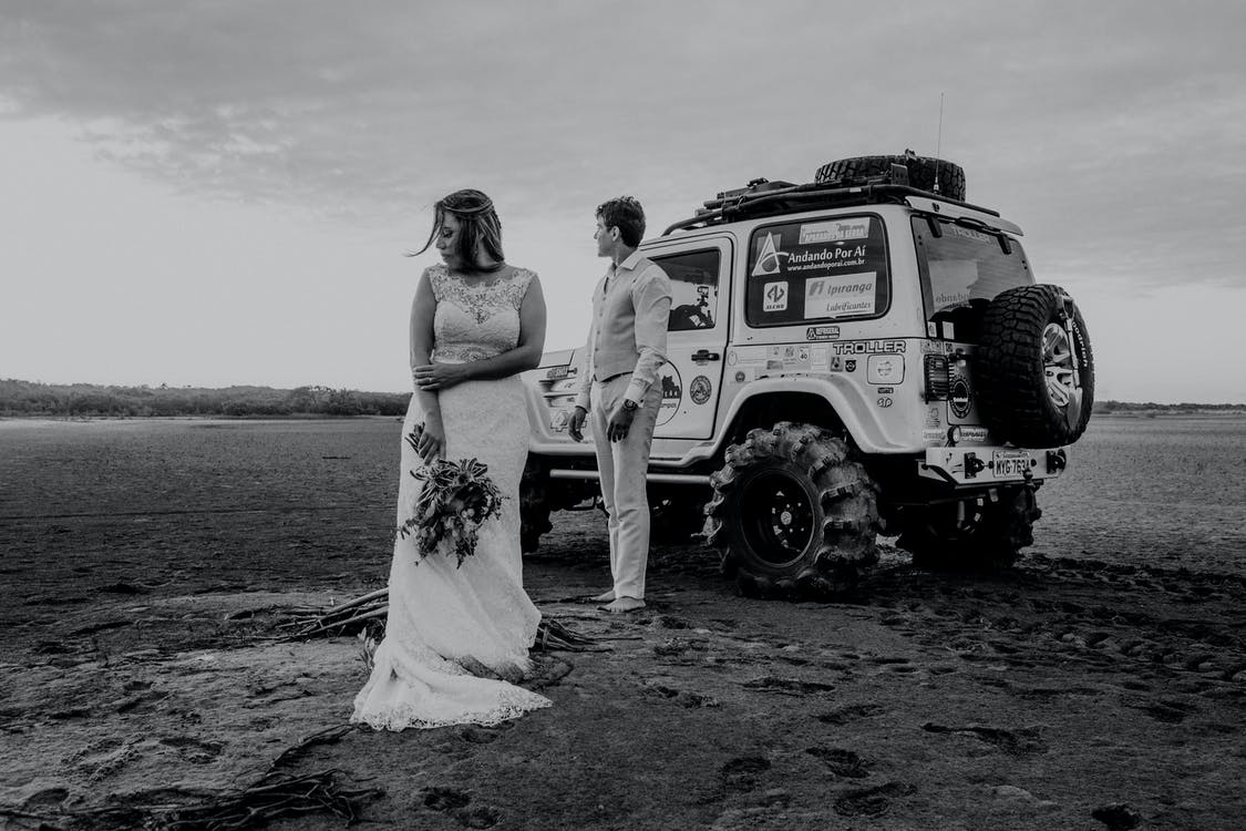 Grayscale Photo of Couple Standing Beside Suv