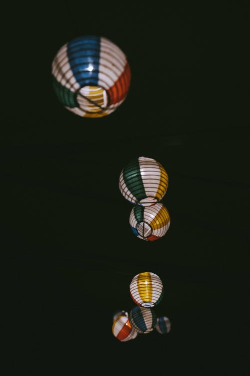 From below of multicolored round shaped lamps with striped ornament on ribbed surface in twilight