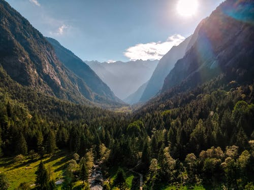 Spectacular view of valley with lush trees between high mounts under cloudy sky with glowing sun