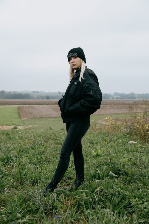 Woman in Black Leather Jacket and Black Pants Standing on Green Grass Field