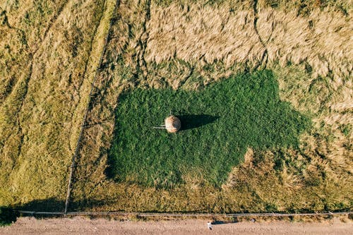 Aerial view of rural land with haystack on green ground near hay field
