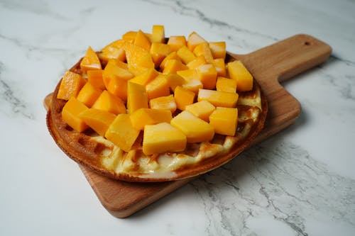 Sliced Mango on Brown Wooden Chopping Board