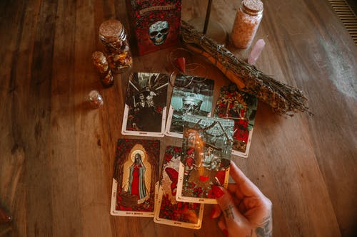 From above of crop unrecognizable tattooed female soothsayer showing tarot card with image above table with decorative bottles and amulet