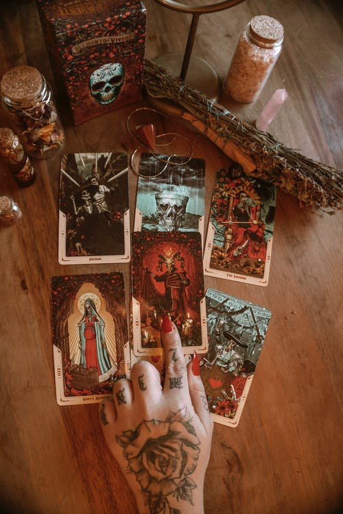 Faceless tattooed fortune teller pointing at tarot card