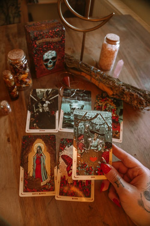From above of crop unrecognizable soothsayer showing tarot card with illustration near dry herb and decorative bottles