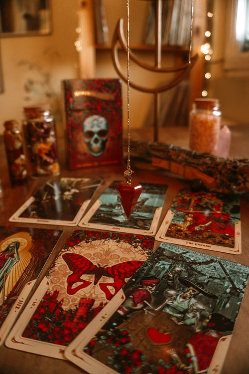 Tarot cards and decorative bottles on table at home