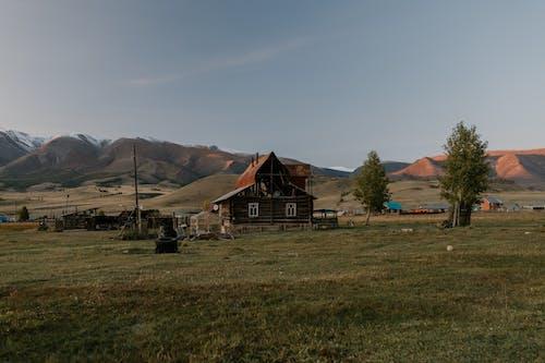 Casa In Legno Marrone E Bianca Sul Campo Di Erba Verde Vicino Alle Montagne Marroni