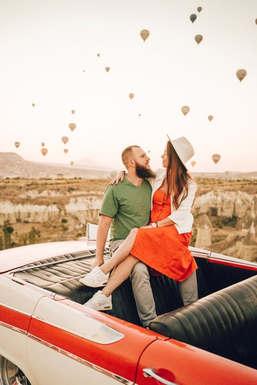 Positive young couple hugging while sitting together in old fashioned cabriolet among balloons in Turkey