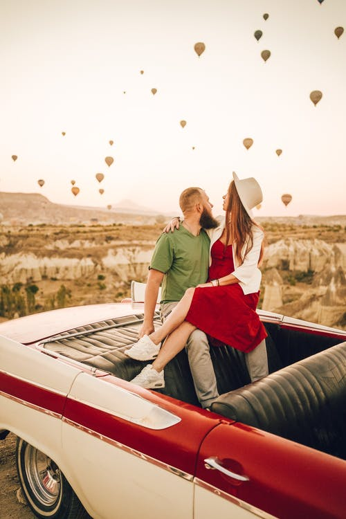 Romantic couple hugging each other while sitting in retro car and enjoying romantic date in Cappadocia