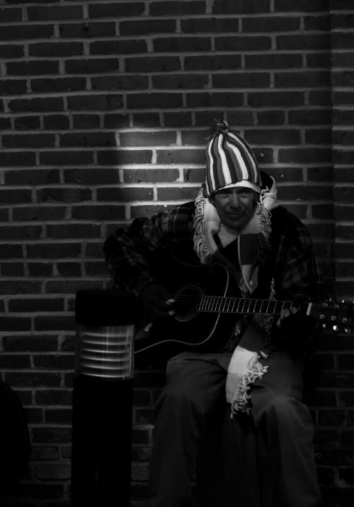 Black and white of man with guitar wearing hat and scarf while sitting near brick wall in street in shade