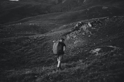 Grayscale Photo of Man in Backpack Walking on Grass Field