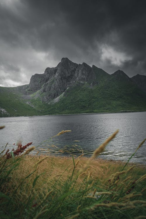 Mountain peak on shore of lake in overcast weather