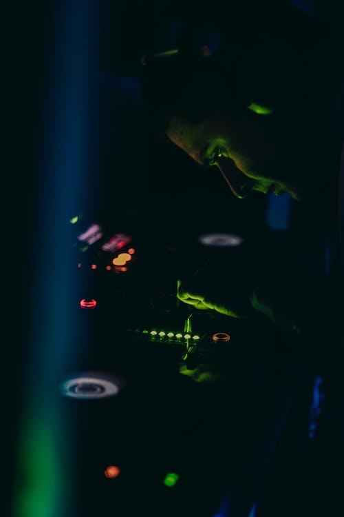 Crop male DJ working on sound mixer in darkness