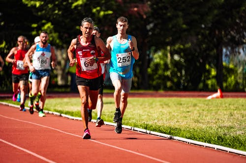 Fast sportsmen running during track and field competition