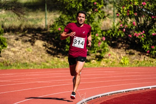 Young focused ethnic male athlete in sportswear running while participating in track and field competition
