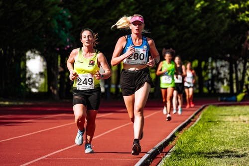 Young concentrated female athletes in sportswear running during track and field competition in stadium