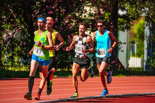 Group of young focused sportsmen in bright active wear running during track and field competition