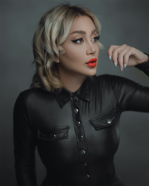 Fashionable woman with makeup against gray background