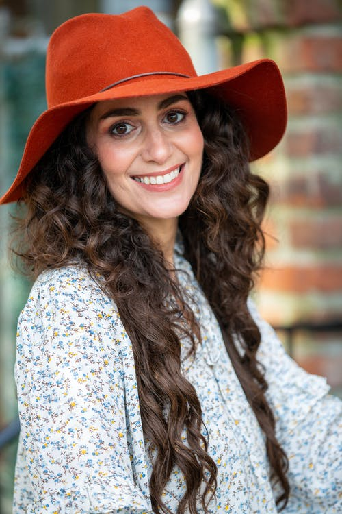 Cheerful woman with wavy hair and hat
