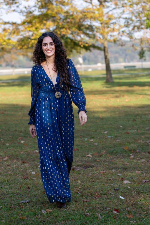 Full length of optimistic female in casual blue dress with toothy smile looking at camera while walking in park during weekend