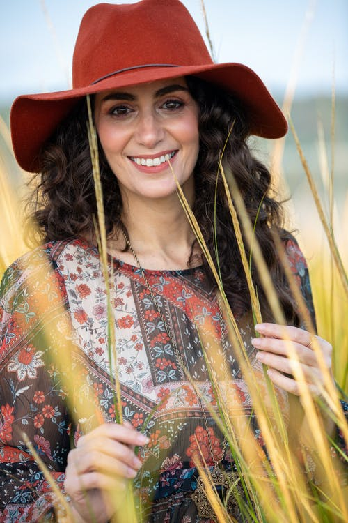 Positive woman in field among dry grass