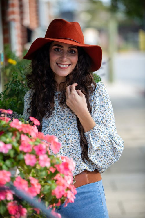 Happy woman near potted flowers on street