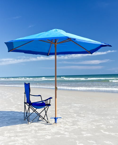 Blue and Black Folding Chair on Beach