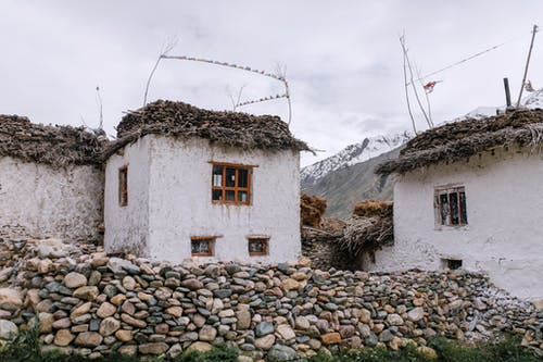 Exterior of grunge white stone shacks with thatch roof surrounded with stone fence and located on rough rocky mountain bottom