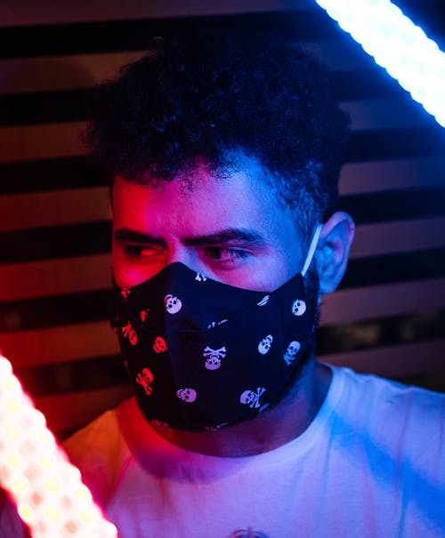 Man in protective mask among neon lamps