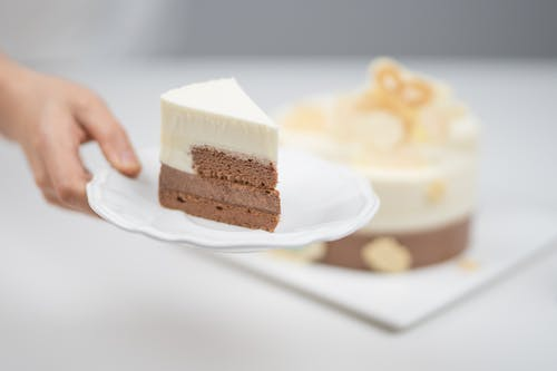 Person Holding Sliced of Cake on White Ceramic Plate