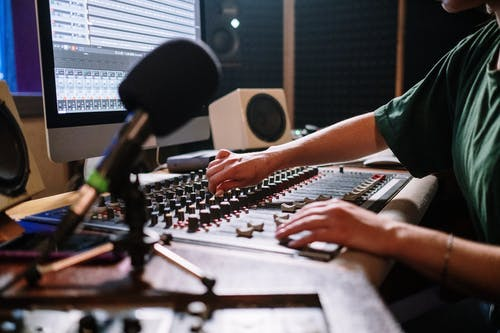 Person in Green Shirt Playing White and Black Audio Mixer