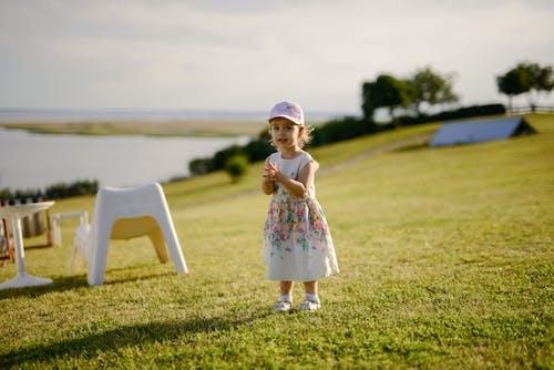 Cute girl standing on grassy river shore