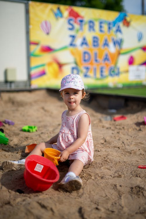 Little girl playing with toys in sandbox
