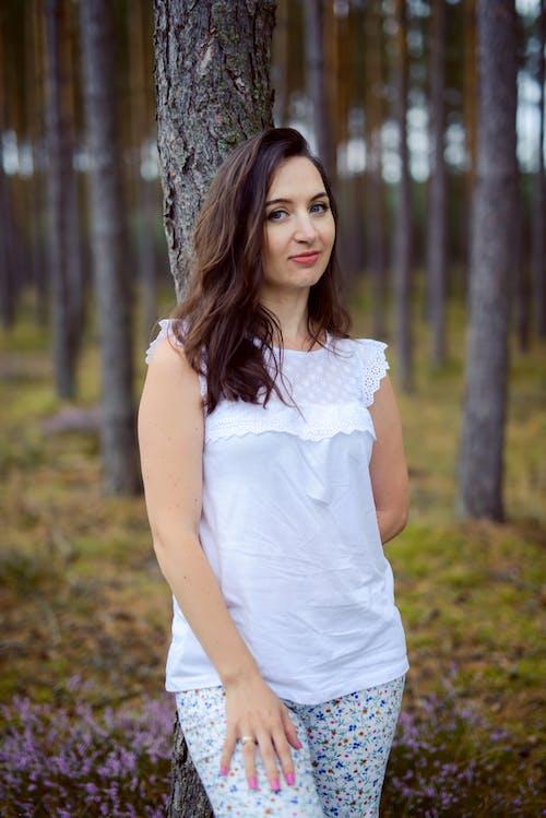 Woman in White Sleeveless Dress Standing Beside Tree
