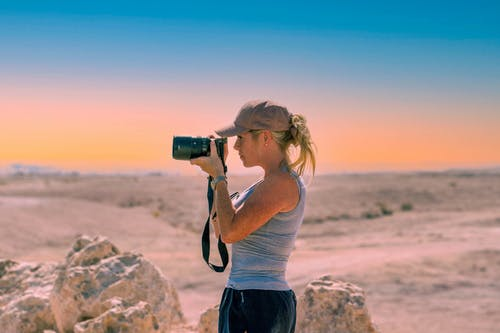 Woman taking photos with camera in desert near stones