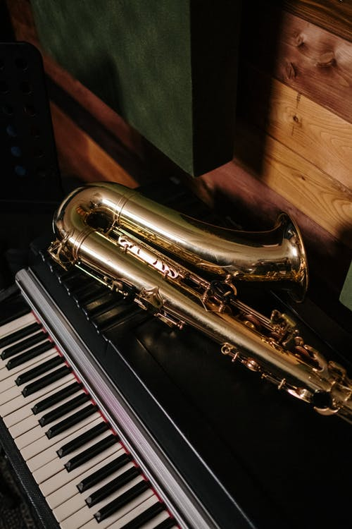 Brass Saxophone on Black and White Piano