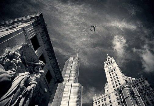 Air Plane Flying over Concrete Buildings and Statues in Grayscale Photography