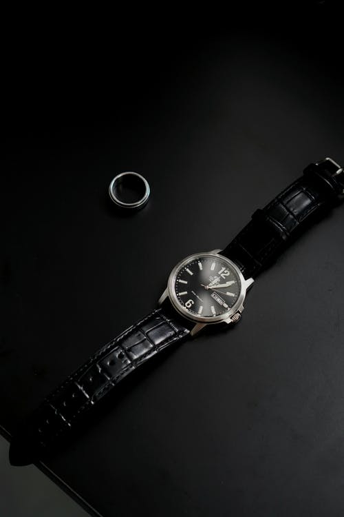 From above of stylish wristwatch with black leather strap near silver ring on table
