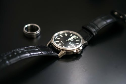 Classy wristwatch near ring for men on black background