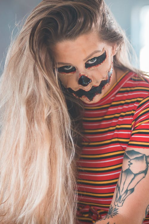 Blond tattooed woman with long hair wearing Halloween makeup looking at camera in daylight