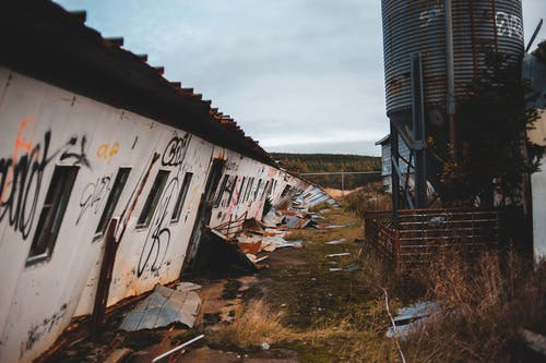 Abandoned buildings with inclined wall in countryside