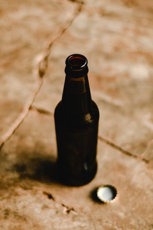 Black Glass Bottle on Brown Sand