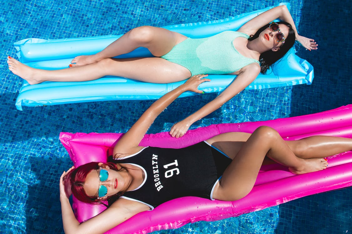 Two Woman Laying Down on Pink and Blue Floaters