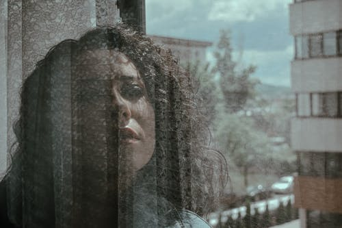 Through window of dreamy female with curly hair looking away while standing behind transparent glass with cityscape on background in sunlight