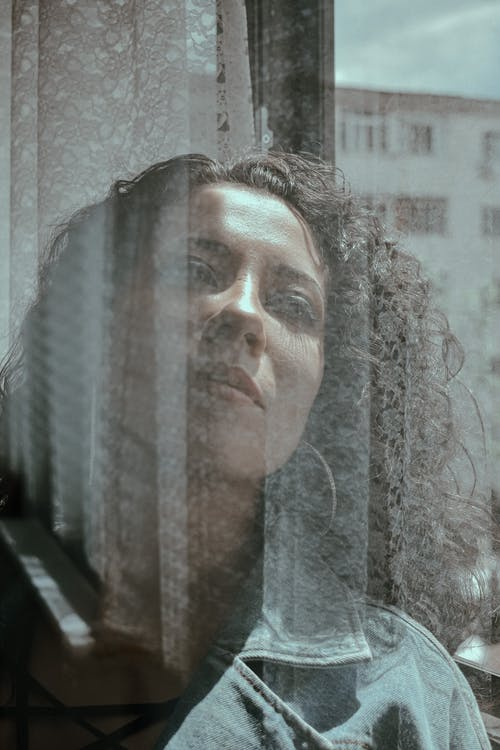 Through glass of dreamy female with dark hair looking out window with reflection on glass surface and building on background